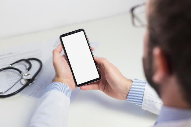 Close-up van een mannelijke arts met behulp van de mobiele telefoon met wit scherm