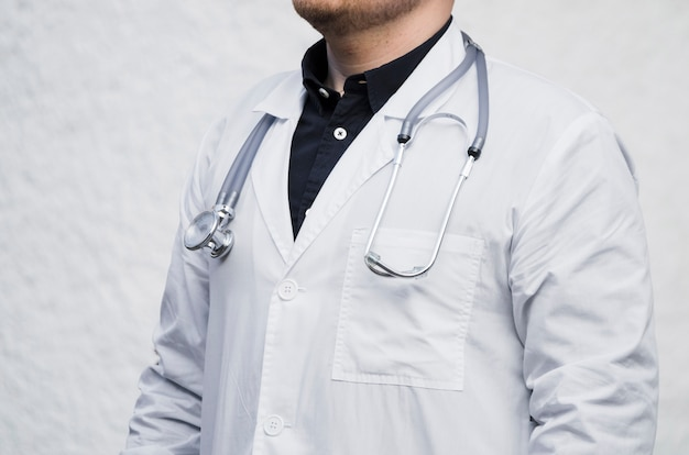 Close-up van een mannelijke arts met een stethoscoop om zijn nek tegen een witte achtergrond