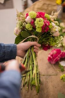 Close-up van een mannelijke bloemist die de stam van boeket met snoeischaar snijdt