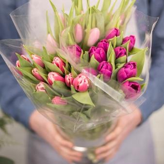 Close-up van een mannelijke bloemist die het roze boeket van de tulpenbloem houdt