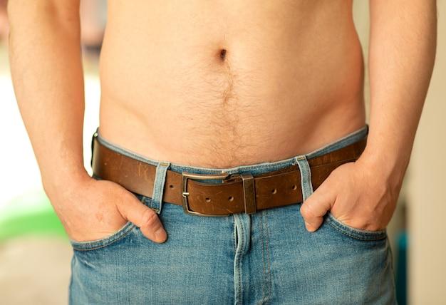 Close-up van een mannelijke buik. een man toont zijn blote buik met zijn handen in de zakken van zijn broekspijkerbroek