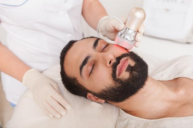 Close up van een mannelijke cliënt ontspannen tijdens rf-lifting gezichtsbehandeling bij schoonheidssalon