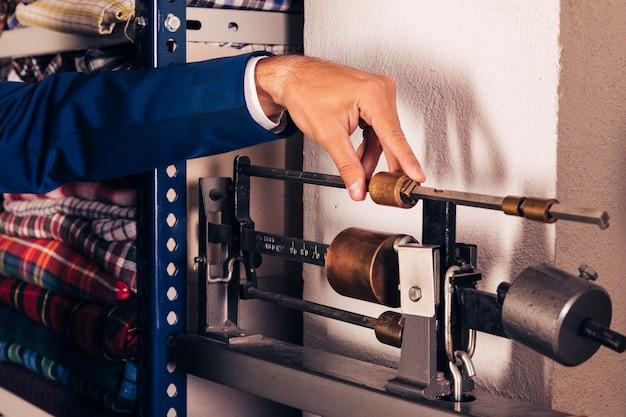 Close-up van een mannelijke manierontwerper die de machine van de stoffen wegende schaal aanpassen
