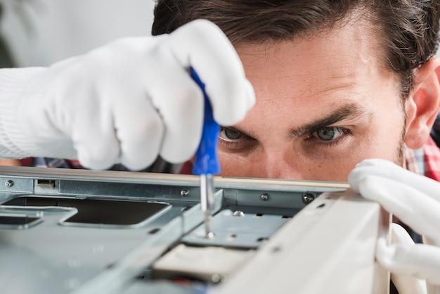Close-up van een mannelijke technicus die cpu met schroevedraaier herstelt