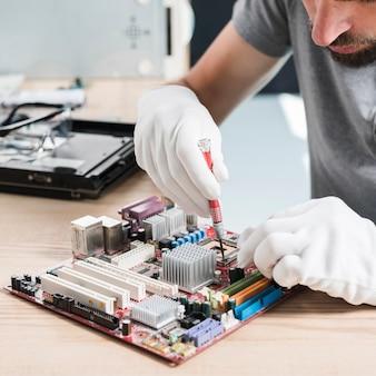 Close-up van een mannelijke technicushand die computermotherboard op houten bureau herstellen