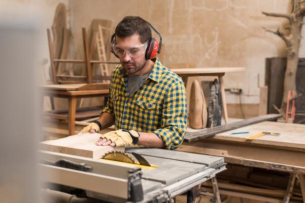 Close-up van een mannelijke timmerman die een houten blok met cirkelzaag in lijst snijdt