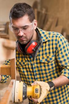 Close-up van een mannelijke timmerman die op het werk hout met behulp van baanschuurmachine oppoetsen