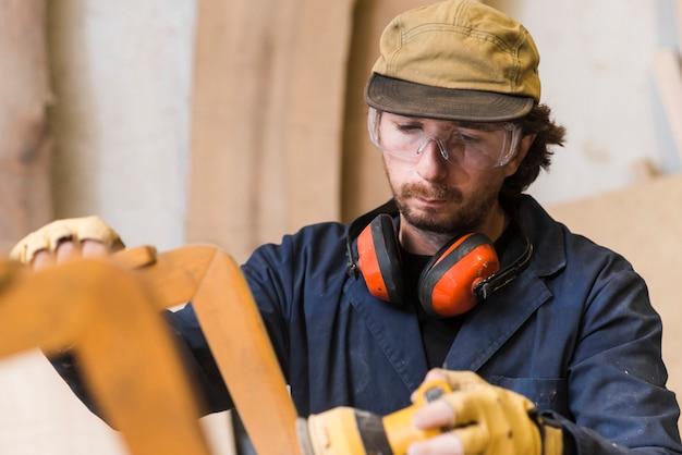 Close-up van een mannelijke timmerman die veiligheidsbril en oorverdediger draagt rond zijn hals die elektrische schuurmachine met behulp van