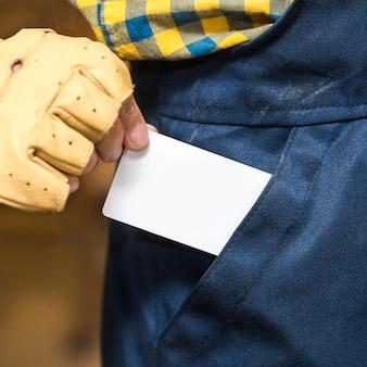 Close-up van een mannelijke timmerman die witte lege kaart uit zijn zak verwijdert