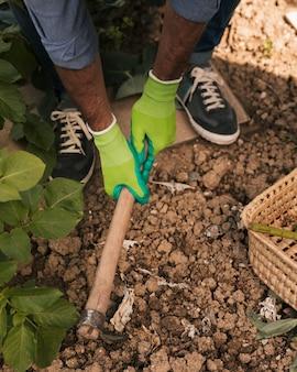 Close-up van een mannelijke tuinman die de grond met schoffel graaft
