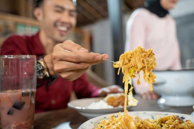 Close up van een mans hand met behulp van een vork die gebakken noedels neemt