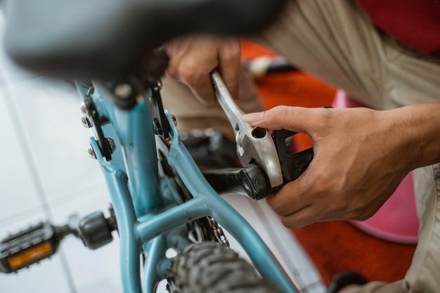 Close up van een mechanische hand die een pedaal installeert met behulp van een moersleutel