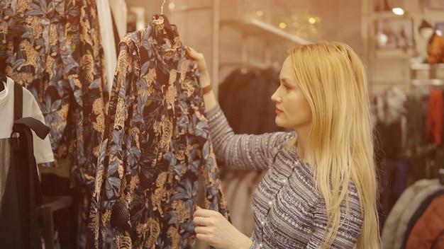 Close-up van een meisje dat een jurk kiest in een warenhuis