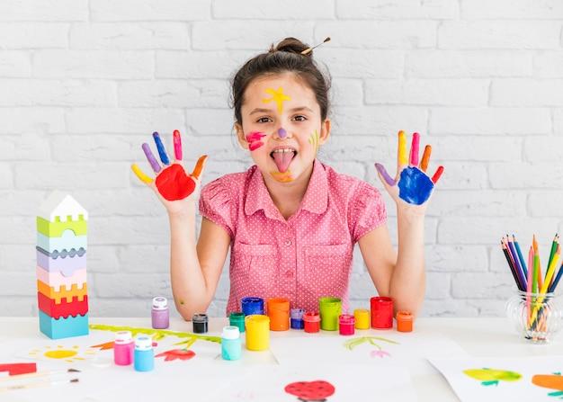 Close-up van een meisje dat haar tong uitsteekt die haar twee geschilderde handen toont