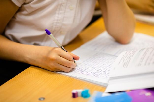 Close-up van een meisje dat in een notitieboekje schrijft