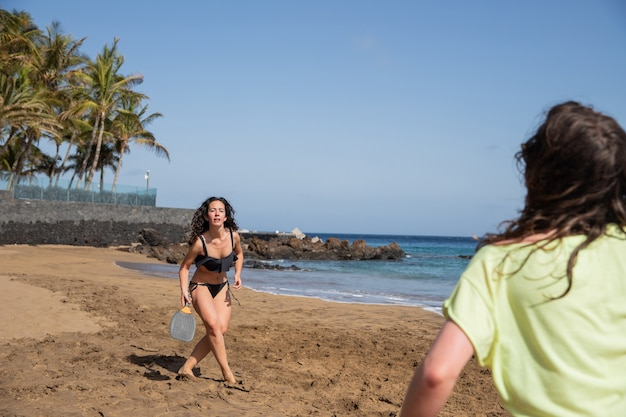 Close-up van een meisje dat strandtennis speelt met haar vriend tijdens hun vakantie op een exotische locatie.