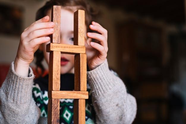 Close-up van een meisje die gestapelde houten blokken in evenwicht brengen