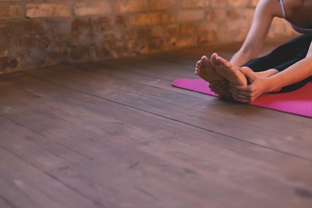 Close-up van een meisje doet een asana naar voren buigen met haar handen naar haar benen