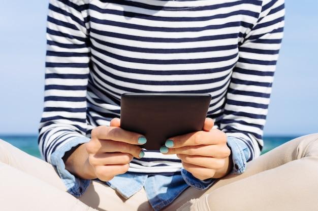 Close-up van een meisje in een gestreept t-shirt met een e-boek in handen op het strand