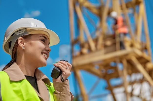 Close - up van een meisje ingenieur met een walkie-talkie in de hand op een bouwplaats in een beschermend vest en helm, in de een werknemer op een gele kraan