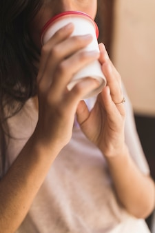 Close-up van een meisje koffie drinken uit afhaalmaaltijden koffiekopje