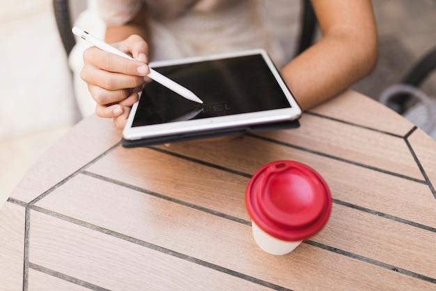 Close-up van een meisje met behulp van de stylus op digitale tablet met afhaalmaaltijden koffiekopje op tafel