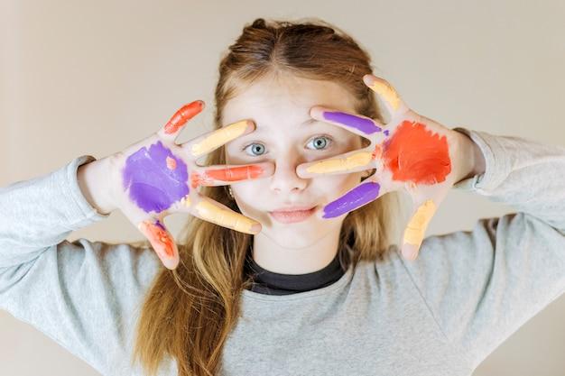 Close-up van een meisje met geschilderde handen camera kijken