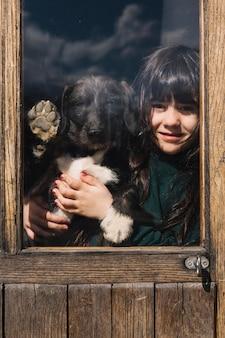 Close-up van een meisje met haar hond die door transparante glasdeur kijkt