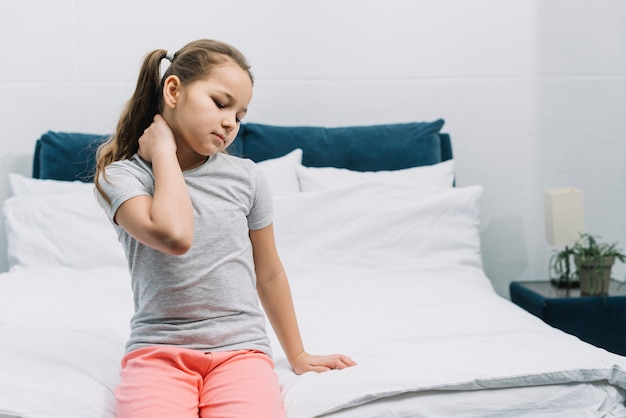 Close-up van een meisje, zittend op bed met pijn in de nek