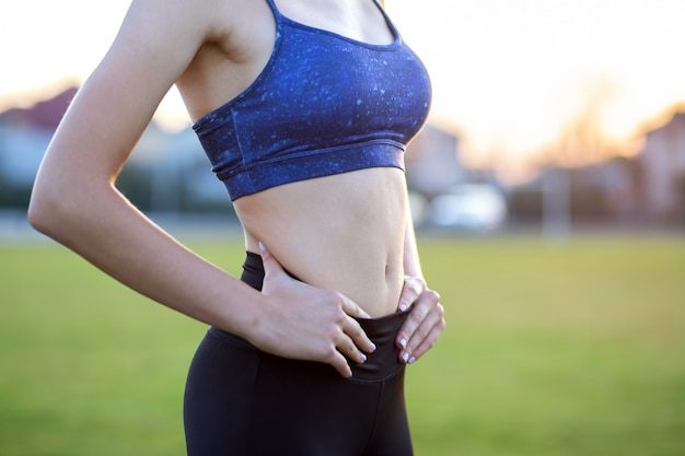 Close-up van een meisjes slank lichaam in sportenkleren. platte buik als gevolg van fysieke training.