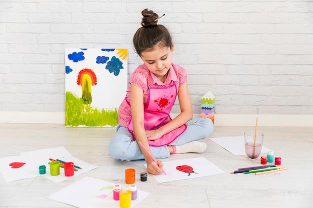 Close-up van een meisjeszitting bij vloer het schilderen op witboek met verf