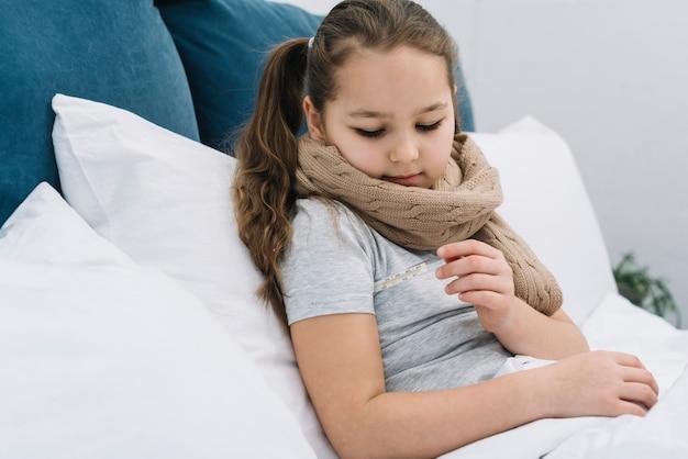 Close-up van een meisjeszitting op bed die de temperatuur met thermometer controleren