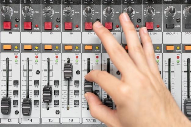 Close-up van een mengpaneel, met de hand egaliserende audiokanalen. professionele opnamestudio. werken in opnamestudio.