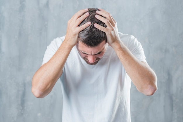Close-up van een mens die aan hoofdpijn tegen grijze achtergrond lijdt