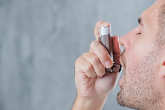 Close-up van een mens die astmainhaleertoestel met behulp van tegen onduidelijk beeldachtergrond