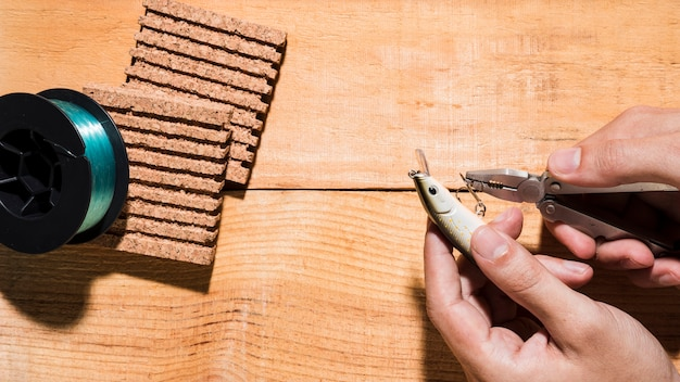 Close-up van een mens die de haak met meer plier dichtbij de spoel en cork raad op houten bureau bevestigt