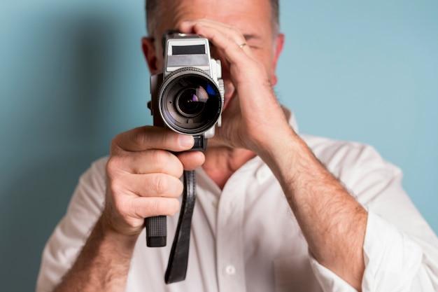 Close-up van een mens die door 8mm filmcamera kijkt tegen blauwe achtergrond