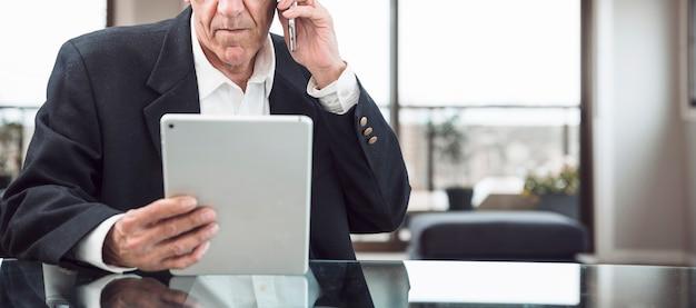 Close-up van een mens die op mobiele telefoon spreekt die digitale tablet in het bureau bekijkt