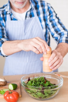 Close-up van een mens die peper met molen toevoegt in groene salade op houten lijst