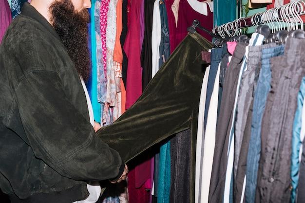 Close-up van een mens die zwarte jeans houdt die op het spoor in winkel hangen