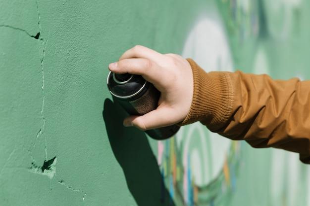 Close-up van een menselijke hand die graffiti met aërosolblikje maakt