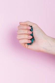 Close-up van een menselijke hand die groene capsule houdt