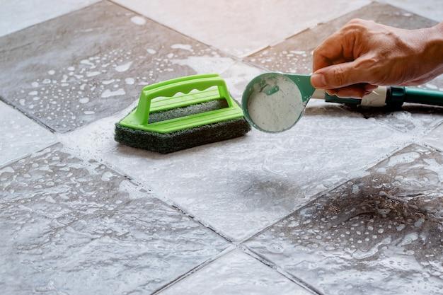 Close-up van een menselijke hand giet wasmiddel op de natte tegelvloer om het schoon te maken.