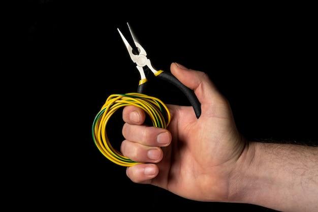 Close-up van een mensenhand die diagonale tang en draad op zwarte achtergrond houden. wordt vaak gebruikt om elektriciteit te repareren