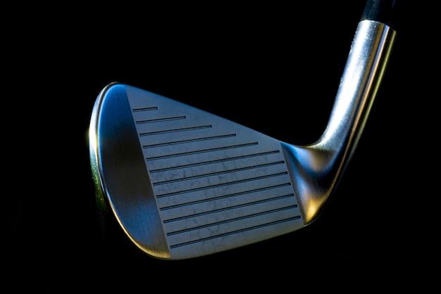 Close-up van een metalen golfclub op zwart