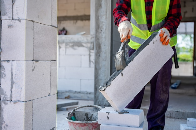 Close-up van een metselaarbouwer die cementmortel gebruikt om de lichtgewicht bakstenen te plaatsen. op bouwplaats