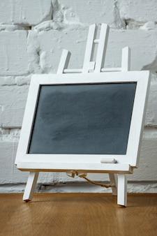 Close-up van een miniatuurschoolbord met krijtvlekken en krijt op een witte bakstenen muur