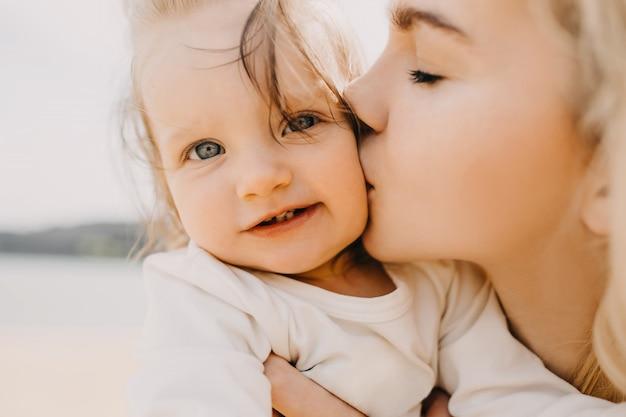 Close-up van een moeder die haar dochtertje op de wang kust