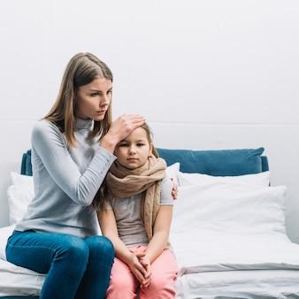 Close-up van een moeder wat betreft haar dochter's voorhoofd die aan koorts lijden