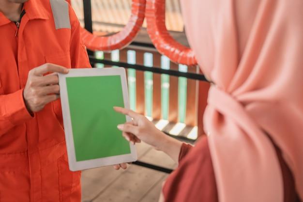 Close up van een monteur in wearpack die een digitale tablet met een klant draagt
